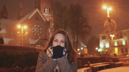 mittens : A young girl on the background of evening city warms up cold hands. In light of the city lights snowing.