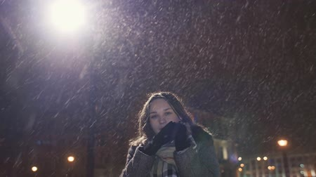 warms : A young girl on the background of evening city warms up cold hands. In light of the city lights snowing.