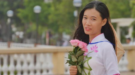 вьетнамский : Vietnam girl in the national costume and dress Ao Dai posing and smiling for the camera. In the hands holding a pink rose.