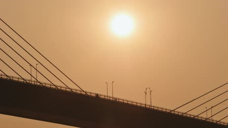 hawser : Steel cables of the bridge against the sunset. Bridge in Ha Long city.