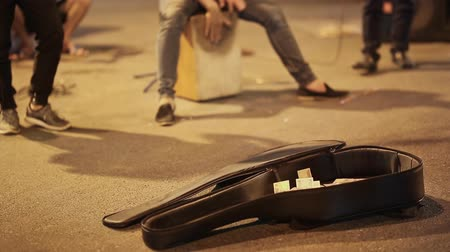 acoustical : Street musicians with guitars playing for people. People throw money to them.
