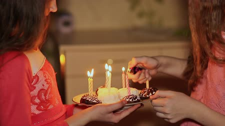 çakmak : Two teenage girls lighting candles on birthday. Cake with candles close-up.