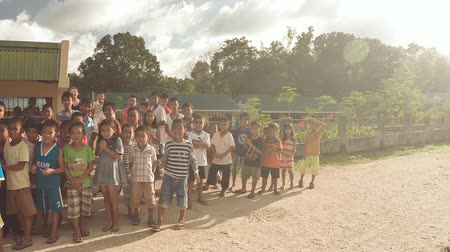 tanítvány : BIABAS, BOHOL, PHILIPPINES - DECEMBER 5, 2015: Children students interact with male tourists.