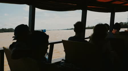 khong : Tourists on a motorized wooden boat sail along the Mekong River. Stock Footage