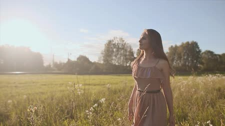 rests : Beautiful girl with long hair goes through the meadow among the flowers. The girl in the rays of the sun.