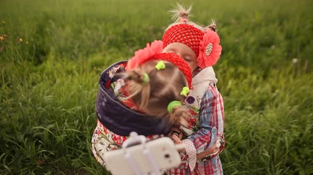 сестра : Two cute little twin sisters photograph themselves on a green meadow, using a phone and a stick for selfie. Mutual embrace and kiss.