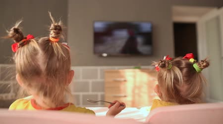 аккуратный : Two little sisters eat at the table and have fun watching cartoons on TV. Back view. Стоковые видеозаписи