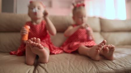 boso : Two little twin sisters in charming red dresses are blowing soap bubbles cheerfully while sitting in the room barefoot. View with emphasis on legs.