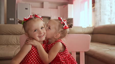 csók : Two cute twin sisters are dressed in red polka-dot dresses. Playing together kiss each other smiling. Stock mozgókép