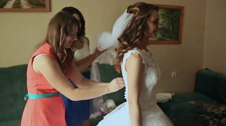 három ember : Beautiful bridesmaids helping the happy bride getting dressed.