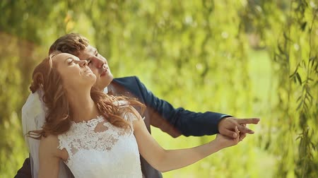 arkasında : Wedding day. Groom behind bride under the green trees. Embrace the flight in the sunlight. Stok Video