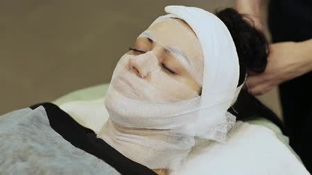 bandaż : Adjustment of gauze tissue on the chin of a girl with cream. A bandage mask using gauze fabric. Wideo
