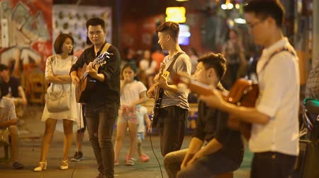 acoustical : HANOI, VIETNAM - OCTOBER 13, 2016: Street performers with guitar, with audience in the background. Stock Footage