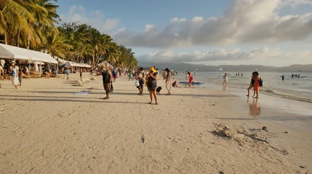 boracay : Boracay, Philippines - January 5, 2018: Holidaymakers on the sunny beach of the island of Boracay. Sand castles with Christmas inscriptions. Positive tourists. Shooting in motion.