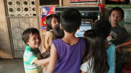 gimnazjum : MANILA, PHILIPPINES - JANUARY 5, 2018: A group of gay Filipino children who gathered around a slot machine on the street of the city of Manila.