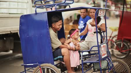 barato : MANILA, PHILIPPINES - JANUARY 5, 2018: Filipino joyful family on a bicycle on Manila street. Local traditional transport.