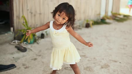 third world : MANILA, PHILIPPINES - JANUARY 5, 2018: A charming Filipino little girl in a white dress cute and fun posing on the camera near the house. Manila.