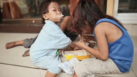 greedily : Hungry homeless children greedily eat the remains of rice on Manila Street. Stock Footage