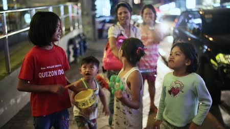 hilltribe : MANILA, PHILIPPINES - JANUARY 5, 2018: Filipino children on the streets of the city are fun to sing and play, using toy musical instruments.