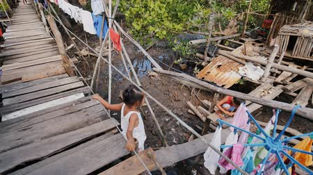 нищета : Coron, Philippines - January 5, 2018: The way of life of children and families in the Filipino slums. Poverty. Children on unsafe wooden bridges from planks on high water. Philippines.