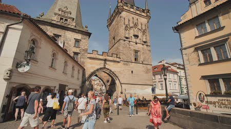 hradcany : Prague, Czech Republic - August 5, 2018: Tourists cross the Charles Bridge on the Path of the Kings leading to the lesser Tower on their way to Prague Castle.