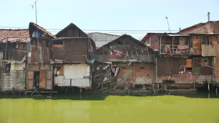 slum house : Jakarta, Indonesia - January 15, 2019: Slum area on the riverbank in Jakarta. Indonesia.