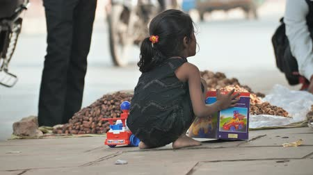 suszone owoce : Agra, India - December 12, 2018: A girl plays next to her grandfather who sells nuts and dried fruits on the outskirts of the road.
