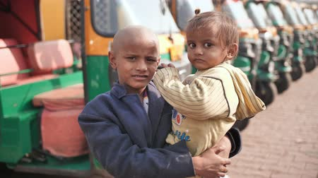 fardo : Agra, India - December 12, 2018: A little beggar boy holds a baby in his arms against the background of a rickshaw.