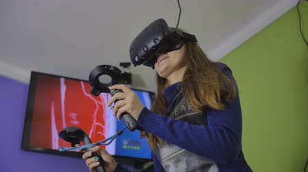 Moscow, Russia - May 19, 2019: A teenage girl plays a virtual game in black virtual reality glasses. Vídeos