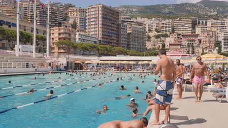 Monaco, Monte Carlo - August 10, 2018: Unidentified people swim and sunbathe at the open air public swimming pool in Monaco.