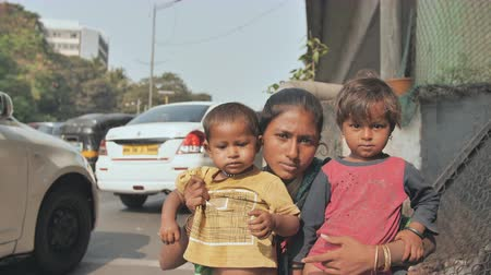 Mumbai, India - December 17, 2018: A homeless young Indian mom with her children on the streets of Mumbai.