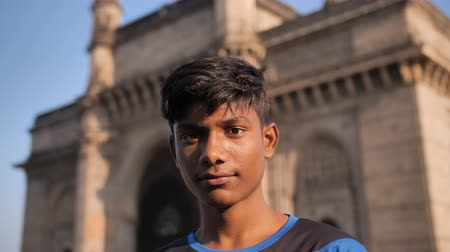 armen over elkaar : Mumbai, India - 17 december 2018: jonge Indiase man op de achtergrond van de Gateway of India in Mumbai.