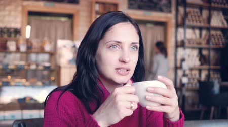 A young woman sits at a table in a cafe and drink coffee Dostupné videozáznamy