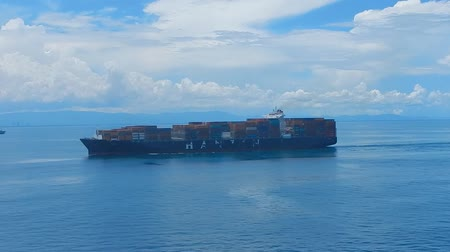 damarlar : Big container vessel passing. Blue sky and clouds in the background.