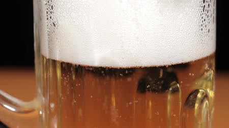 pint glass : Pouring beer in glass on black background full HD video Stock Footage