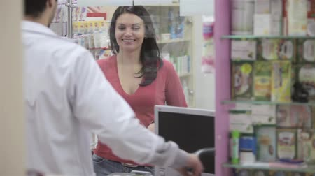 raflar : Happy woman Paying for pills in pharmacy