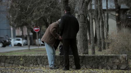 caregiver : Old men thanking young men for helping him Stock Footage