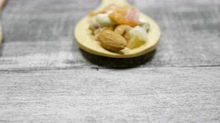 cukrozott : Healthy different type of nuts and sweet in wooden spoon on wooden background.