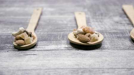 mandula : Different type of nuts and sweet in wooden spoon on wooden background.