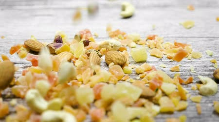 nutrição : Slow motion of Healthy type of nuts and sweet on wooden background. Dry healthy snack food Vídeos