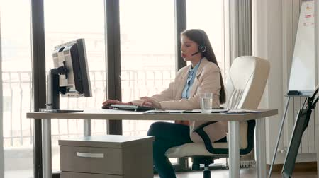 képviselő : Zoom in shot of young beautiful businesswoman talking on the headset in the office. Sales and communication