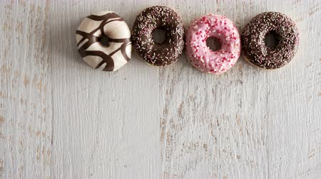 borrifar : Stop motion of donuts on white wooden background. Delicious junk food