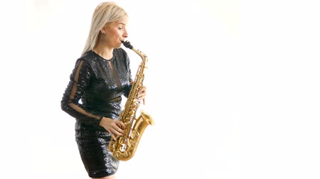 fife : Woman in black concert dress playing a melody on saxophone isolated over white background in studio