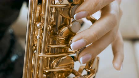 instrumentos : SLOW MOTION close up of woman playing on saxophone. Jazz player rehearsing