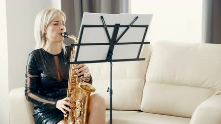 saxofone : Slow motion of beautiful saxophonist woman playing at the sax in the living room. Dolly shot Stock Footage