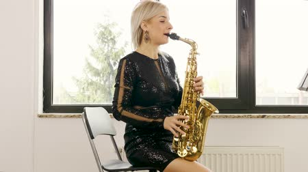 saxofone : Slow motion of jazz saxophone woman player. She is playing in the living room