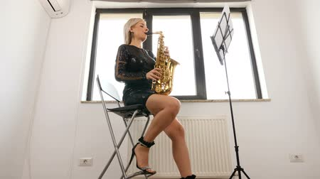saxofone : Woman saxophonist playing at the sax in the living room. Jazz player Stock Footage