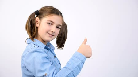 igen : Cute little girl showing thumbs up sign on gray background in studio