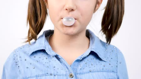 камедь : Slow motion close up portrait of cute girl chewing gum and blowing a bubblegum bubble ballon on gray wall Стоковые видеозаписи