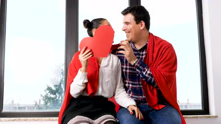 csatlakozott : Slow motion of couple playing with a red papper heart next to a big window Stock mozgókép
